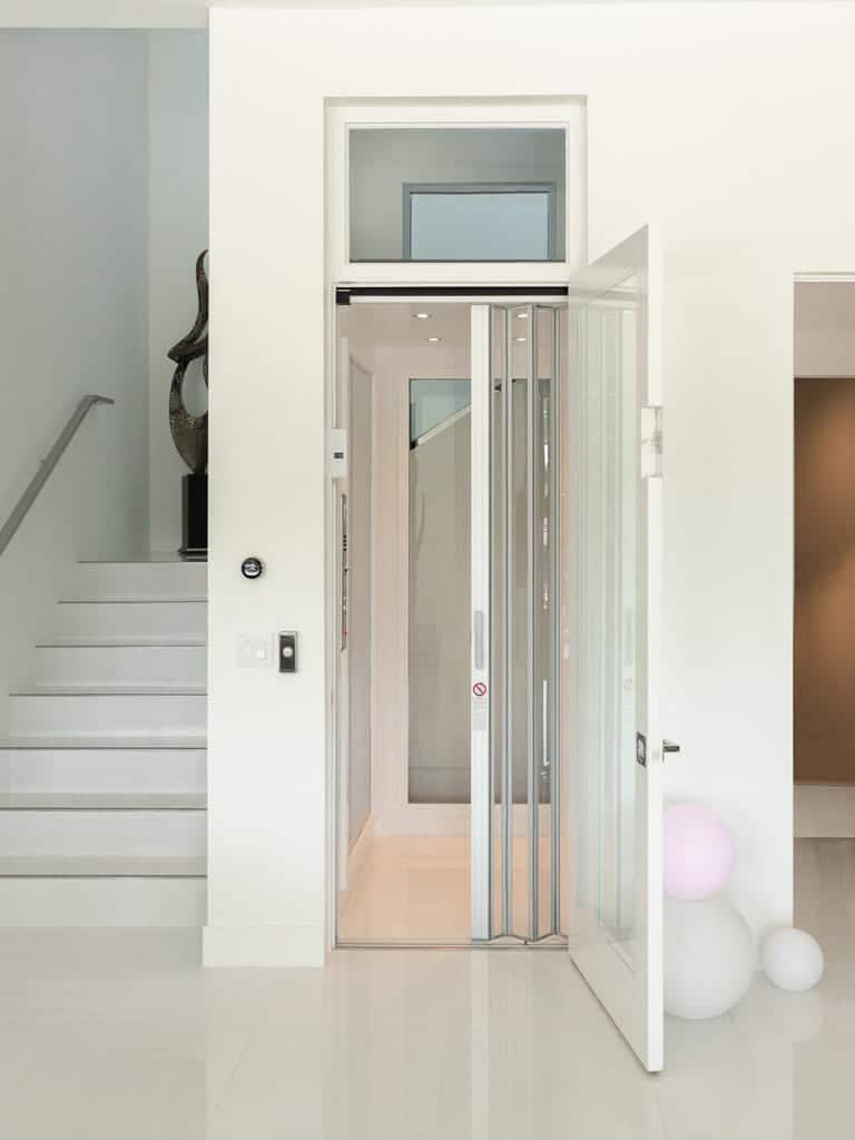 white Home Elevator installed by stairs